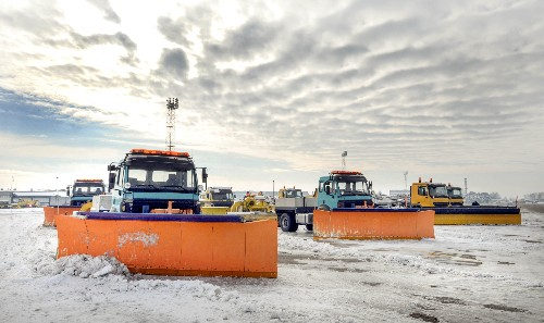 Three plow trucks stand ready to help businesses with commercial snow removal