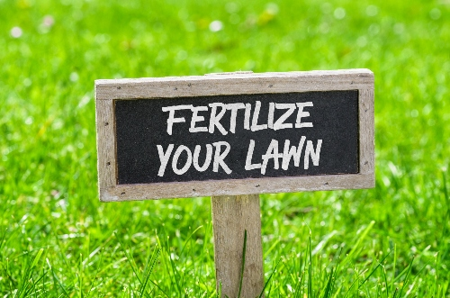 "A sign on a bright green lawn reads ""fertilizer your lawn."""