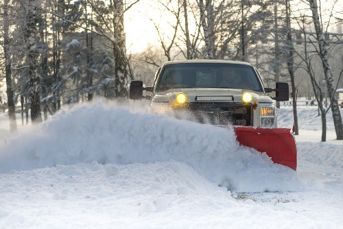 A truck plows property as part of the winter weather management.